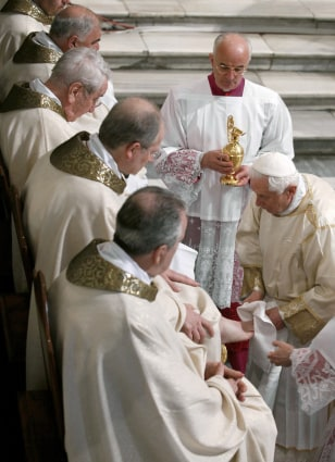 Image: Pope Benedict XVI washes the foot of a priest at a ceremony marking Jesus' last supper