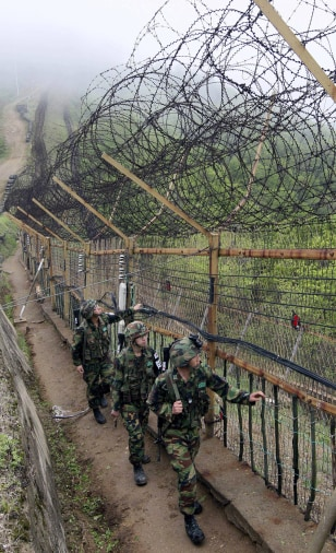 Image: South Korean soldiers check fences set up along the demilitarized zone
