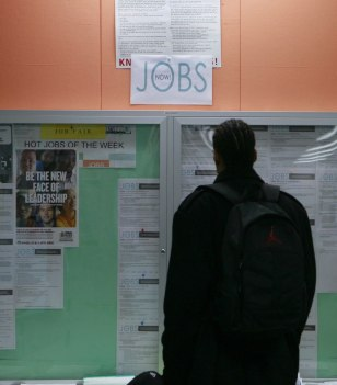Image: File image of a man looking at employment opportunity postings in San Francisco