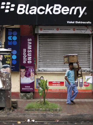 Image: A man with his belongings walks past a closed store selling mobile phones in Kolkata