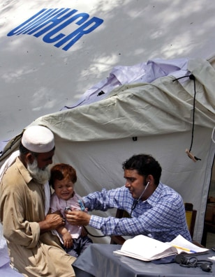 Image: A flood victim gets medical treatment at a tent camp in Nowshera, Pakistan