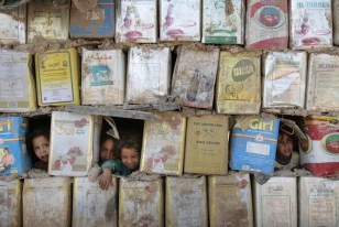 Image: Displaced Iraqi children in hut made of cans