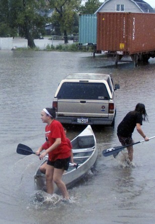 Image: Olivia Leavitt and Kenzie Kubis, canoe through the flooded streets of Arcadia, Wis.