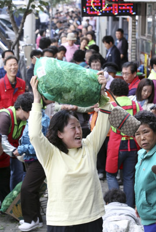 Image: People stand in queues as they wait for their turn to buy cabbages subsidized by Seoul city hall office, at a market in Seoul