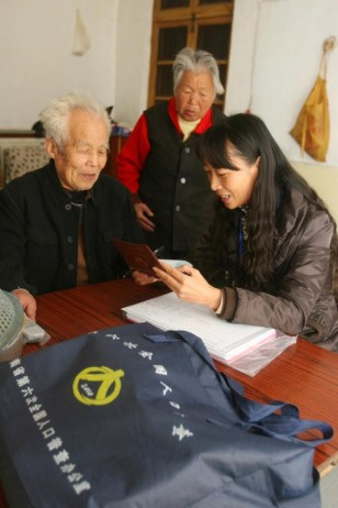 Image: Census workers talks to residents in China