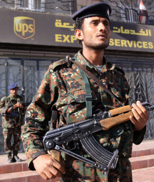 Image: Yemeni police stand guard next to the closed UPS office in San'a, Yemen