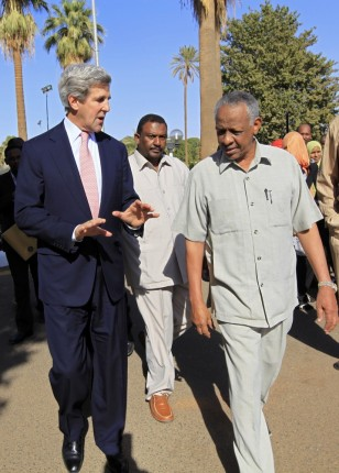Image: Presidential adviser Nafi Ali Nafi walks with U.S. Senator Kerry after meeting at the presidential palace in Khartoum