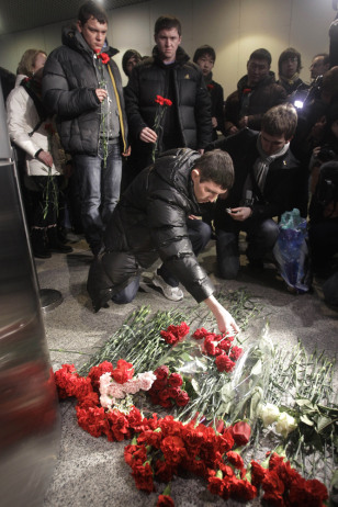 Image: People lay flowers at the site of a blast at Domodedovo airport near Moscow