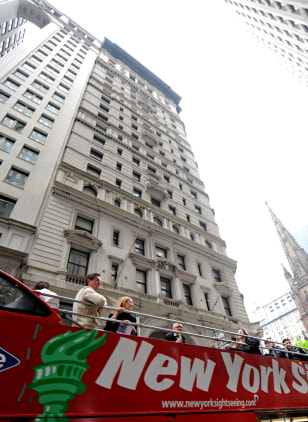 Image: A sightseeing bus drives past the building where former IMF head Dominique Strauss-Khan is being held under house arrest after posting bail in New York