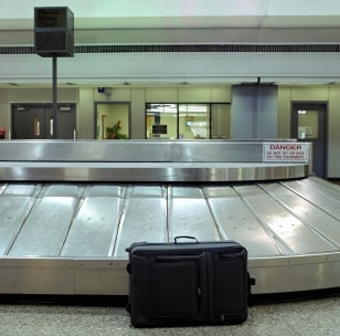 Image: Unattended suitcase sitting in baggage claim at airport