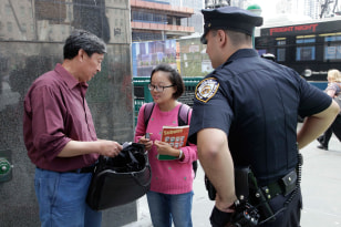 Image: A New York City police officer stops Xiang Mao, left, and Lexi Li along the perimeter of the World Trade Center.
