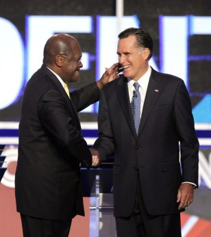 Image: Herman Cain greets Mitt Romney before a Republican presidential debate Tuesday.