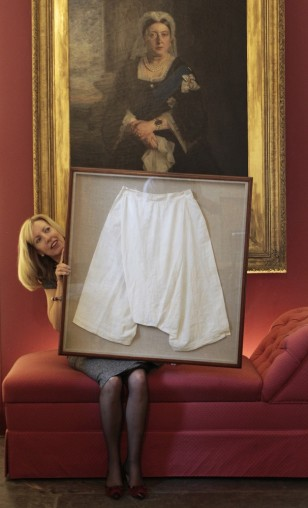 Image: Kate Bain from Lyon and Turnbull auctioneers poses for photographers with a framed pair of silk bloomers that once belonged to Queen Victoria.