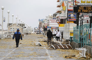 Image: Residents walk by debris on the boardwalk after Hurricane Sandy in Ocean City, Md.