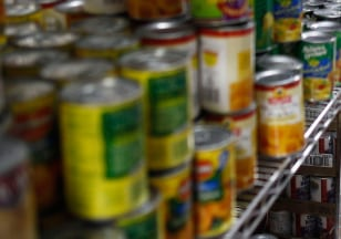 Image: A woman looks at canned food items at the Food Bank For New York City Community Kitchen & Food Pantry of West Harlem in New Yo