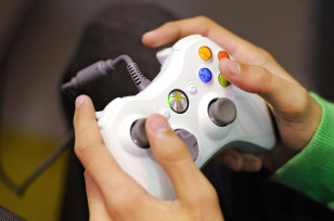 Image: A woman plays with an XBOX games console