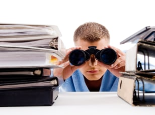 Image: Business section - man with binoculars surrounded by notebooks and folders.