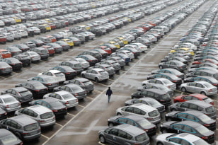 Image: An employee walks past new cars at the parking lot of Changan Ford Mazda Automobile Co. Ltd