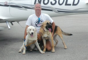 Image: Pilot Jeff Bennett with two dogs outside his plane
