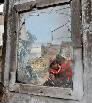Image: An ethnic Uzbek woman and her son captured in a broken mirror