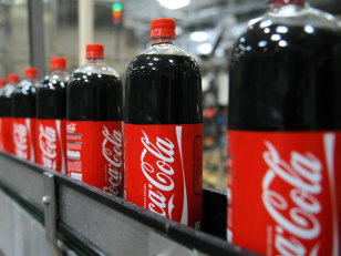 Image: Coca-Cola bottles on an assembly line at a Coca-Cola bottling plant.