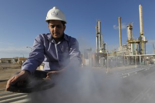 Image: A Libyan oil worker, works at a refinery inside the Brega oil complex