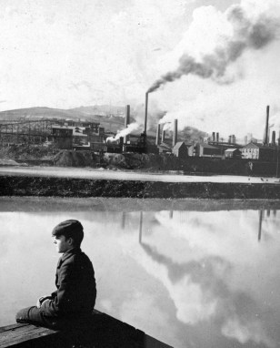Boy seated with smelter smoke in background