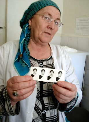 Image: Leila Pliyeva holding photos of her son Alikshan Pliyev