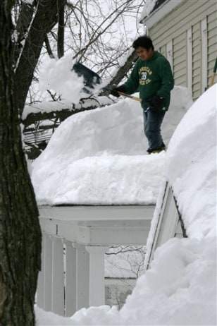 Image: Man clears snow from roof