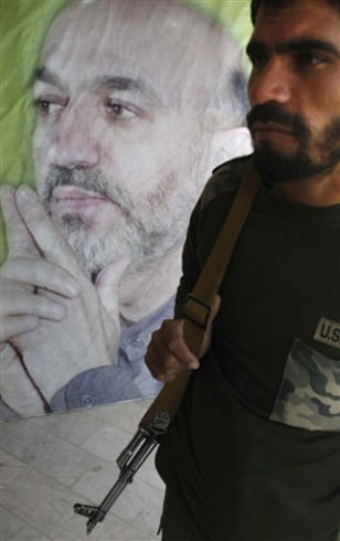 Image: Afghan security man stands, near an election poster of Afghan President Hamid Karzai
