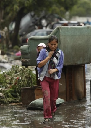 Image: Woman, carrying a baby, walks in a flooded street