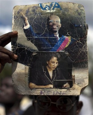 Image: A protester holds a picture of Haiti's ousted President Jean-Bertrand Aristide and his wife, Mildred Trouillot Aristide