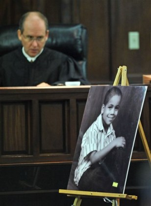 Image: Judge Stephen G. Scarlett looks at a photo of Christopher Barrios, 6,