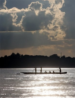 Image: Congolese men push a pirogue across the Congo river between Congo's capital Kinshasa, and Brazaville