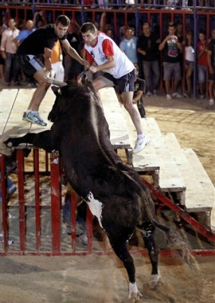 Image: A reveler runs away from 'Raton' the killer bull on Sunday