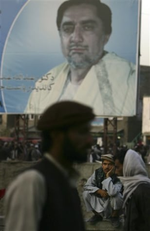 Image: An Afghan man sits under a giant portrait of Abdullah Abdullah