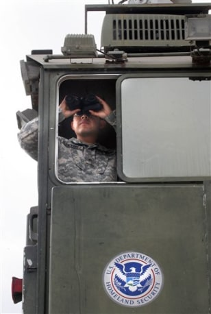 Image: A Texas National Guardsman surveys the terrain from a Border Patrol Skybox near the Hidalgo International Bridge in Hidalgo, Texas