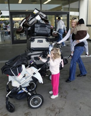 Image: Blair Weisbecker carries her son Kaiden, 4, as her daughter, Makena, pushes her 5-month-old baby brother Lincoln