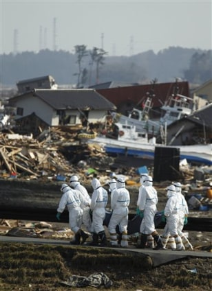 Image: Japanese police officers carry recovered body