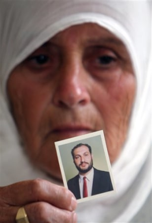 Image: Wajeeha Allawi holds an image of her son, Samer Allawi