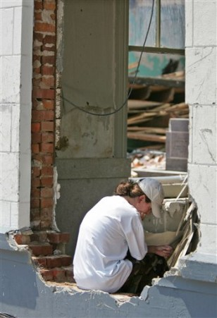 Woman sits inside damaged bank building