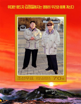 "Image: a commemorative postage stamp featuring late North Korean leader Kim Jong Il and his son Kim Jong Un is shown. The words on the top read ""The great leader comrade Kim Jong Il will always be with us."""