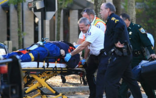 Image: Paramedics transport a gunman who shot himself at a school board meeting in Panama City, Fla.