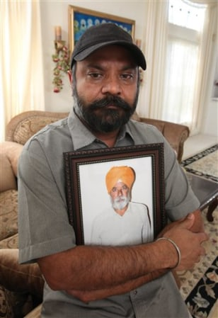 Image: Kamaljit Atwal clutches a photo of his slain father, Gurmej Atwal