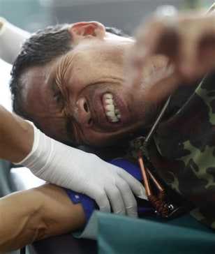 Image: Medical personnel examine an injured Thai soldier