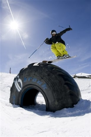 Image: skier going over a truck tire at Breckenridge Ski Resort