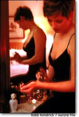 Image: Woman and Perfume - In a candlelit bedroom, a woman applies perfume to her wrist