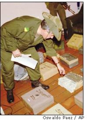 Colombia's police chief Gen. Jose Serrano examines millions seized at a Cali drug cartel house