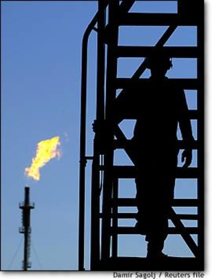 Image: Iraqi Man Climbs Structure At Oil Refinery Outside Baghdad