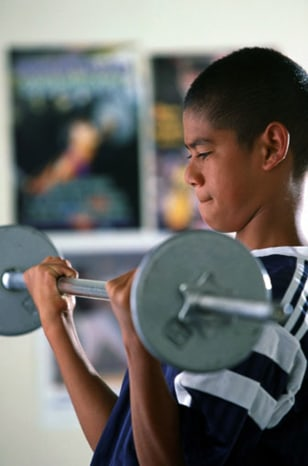 Image: Teen boy lifting weights.